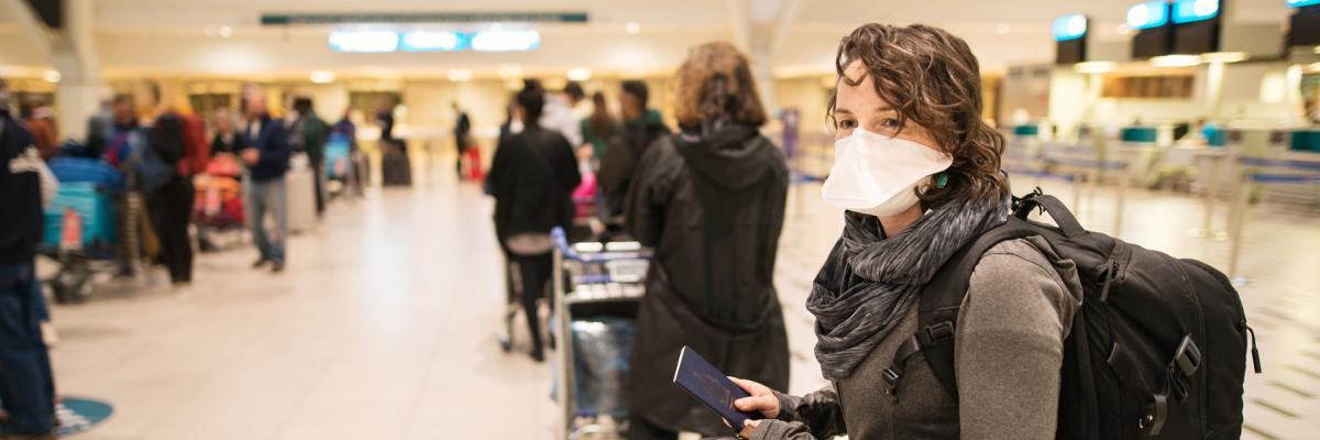 Woman waiting at a queue in an airport wearing a mask.