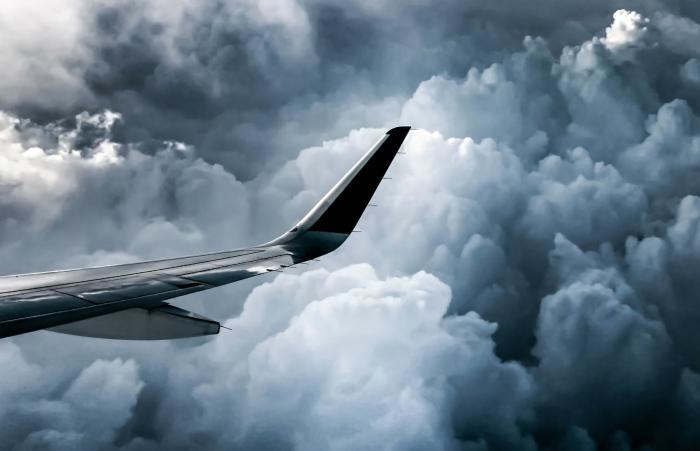 Airplane flying through clouds in severe weather.