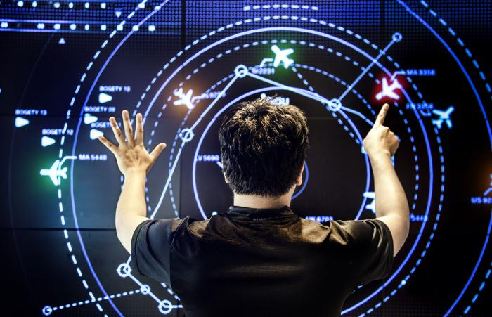 An air traffic controller controlling a virtual airspace using hand gestures.